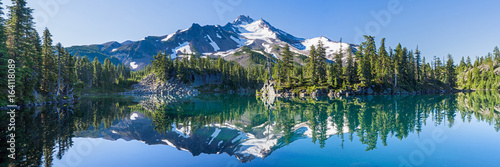 Photo Stands Khaki Volcanic mountain in morning light reflected in calm waters of lake.