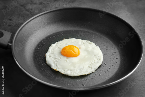 Door stickers Egg Homemade over easy fried egg in pan on dark background