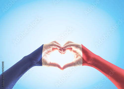 Obraz France national flag pattern on people's hands in heart shape on blue sky background (isolated with clipping path) - fototapety do salonu