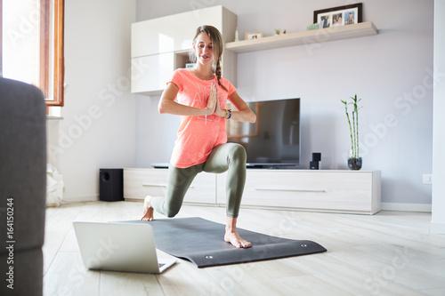 Valokuva  Ragazza fa yoga a casa con pc