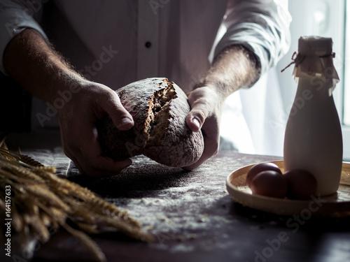 Aluminium Prints Bestsellers Man bakes fresh bread on kitchen table