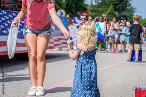 Cuadros en Lienzo handing candy to little girl at hometown 4th of July parade