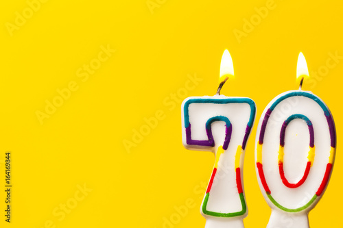 Fotografia  Number 70 birthday celebration candle against a bright yellow background