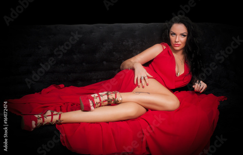 Photo Portrait of sexy brunette in red dress on the black