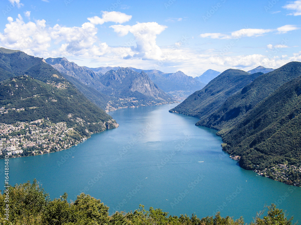 Aerial view of Lugano city with houses, lake and cityscape, and alpine Swiss mountains in Switzerland