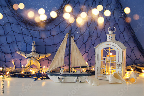 Poster Indiens Magical lantern with candle light and wooden boat on the shelf. Nautical concept