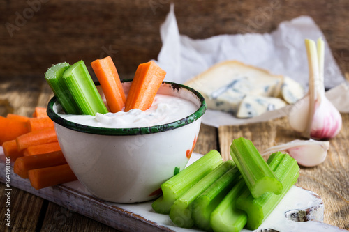 Mug of blue cheese garlic dip sauce with celery and carrot sticks Canvas Print