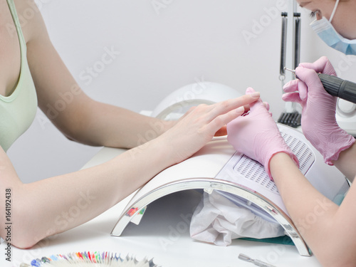Girl in gloves handles nails with a milling cutter for manicure