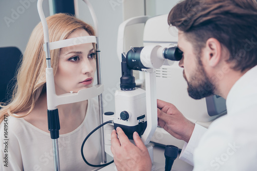 Fotografía  Concentrated brunet bearded optician with non contact tonometer is checking blond`s lady patient intraocular pressure at eye clinic