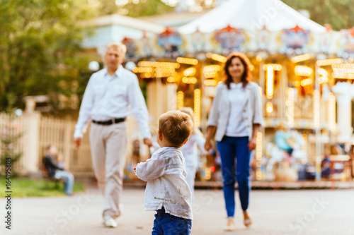Photo sur Toile Attraction parc Cute toddler boy running in amusement park with her family on background. Family vacation concept.
