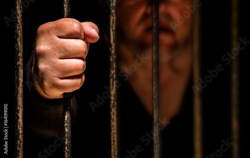 Fotomural  ein Mann ist im Gefängnis eingesperrt, seine Faust umschlingt das Gitter der Gef