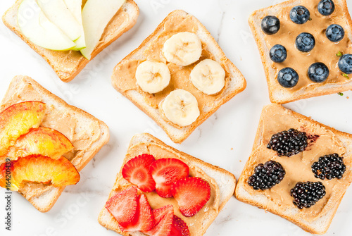 Traditional American and European summer breakfast: sandwiches of toast with peanut butter, berry, fruit apple, peach, blueberry, blueberry, strawberry, banana. White marble table. copy space top view