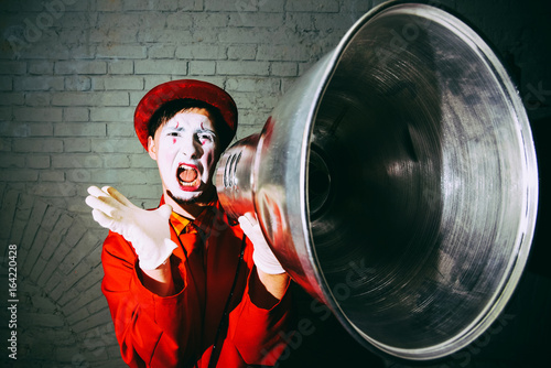 Fotografie, Obraz  Mime took a metal lampshade and pretends to shout into the shout