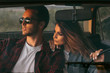 Attractive portrait of romantic young couple going on a long drive in car on sunset light. Handsome young man wearing sunglasses with his beautiful girlfriend on a road trip. Lifestyle concept.