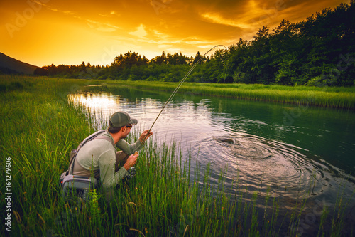 Acrylic Prints Fishing Fly fisherman fishing pike in river
