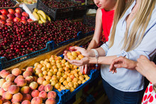 Three Young Women At Grocery Market. Women Choose Fruit.