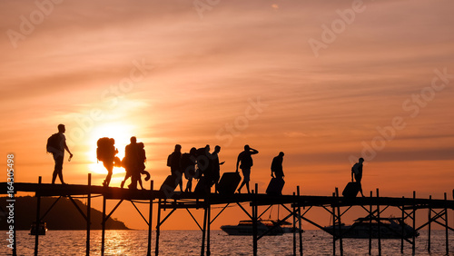 Fototapety, obrazy: Silhouettes of the backpackers walking along the wooden pier to the ferry on beautiful sunset time. Tourists with bags walk along the Bang Rack pier to the ferry to Phangan island