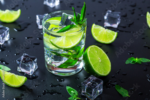 Obraz na plátně Mojito cocktail with lime, ice cubes and mint in highball glass on a black backg