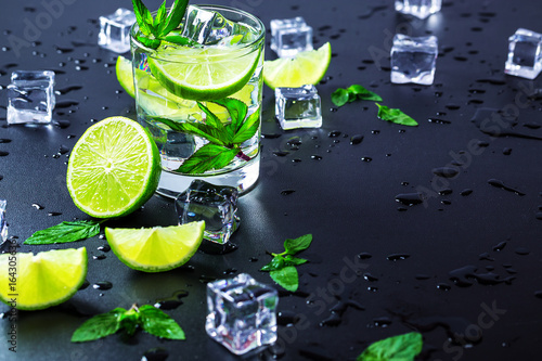 Fotografie, Obraz Mojito cocktail with lime, ice cubes and mint in highball glass on a black backg