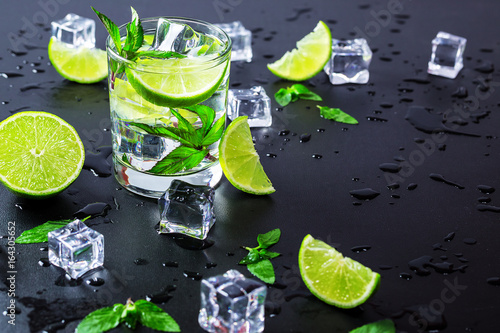 Fototapeta Mojito cocktail with lime, ice cubes and mint in highball glass on a black backg