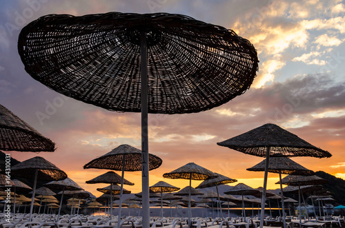 Papiers peints Cappuccino Colorful sunset on the beach against the background of the sea and the mountains. Rest on the sea. Beach umbrellas and skiers.