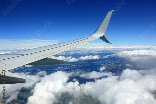 Widok skrzydła samolotu, chmur, i obszarów zabudowanych z lotu ptaka. - 164312078