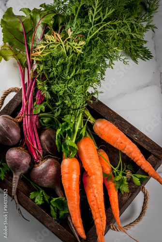 Keuken foto achterwand Groenten Summer, autumn harvest. Fresh organic farm vegetables in a wooden box on a white marble table - beets, carrots, parsley, tomatoes. Copy space top view