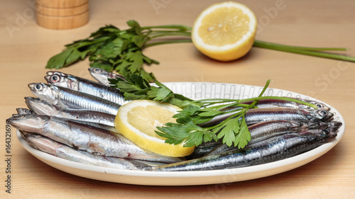 """Oval dish full of fresh Mediterranean anchovies, known as """"boquerones"""" in Andalusian gastronomy, beside parsley and lemon slices. Mediterranean diet"""