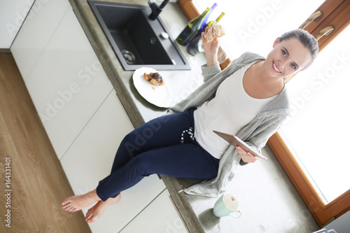 Photographie  Beautiful young woman using a digital tablet in the kitchen.