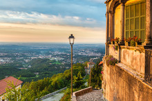 Sacro Monte Of Varese (Santa Maria Del Monte), Medieval Village, Italy. Picturesque View Of The Final Part Of The Sacred Road With The 14th Chapel, Varese, On The Horizon The City Of Milan, At Dawn