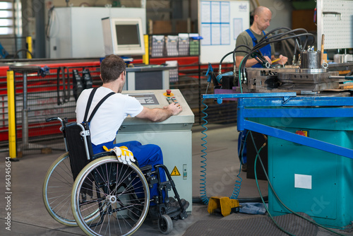 Obraz disabled worker in wheelchair in factory and colleague - fototapety do salonu