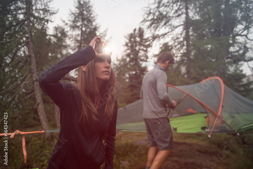 Obraz Woman turning on headlamp flashlight near hanging tent camping. Group of friends people summer adventure journey in mountain nature outdoors. Travel exploring Alps, Dolomites, Italy. - fototapety do salonu