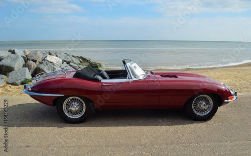 Fotomural Classic Dark Red British Sports  Convertible Motor Car Parked on Seafront Promenade