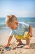 sea ,day,beach ,sand boy playing with a toy