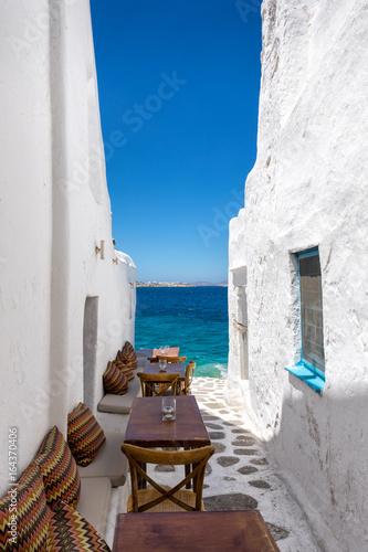 Obraz na płótnie Tische und Stühle in einer Gasse am Meer in Mykonos, Kykladen, Griechenland