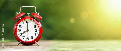 Obraz Summertime - web banner of a retro red alarm clock on green background - fototapety do salonu