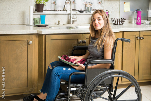 Photo  Disabled woman doing house chores