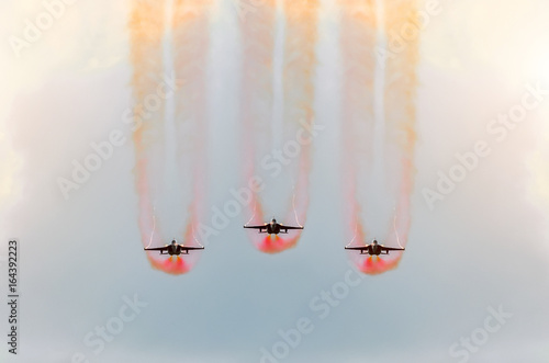 Fototapeta  Two fighter jets fly together with red smoke