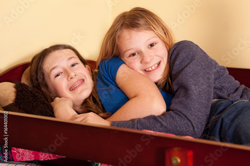 Fotografie, Obraz  Two teen girls snuggled in bed.