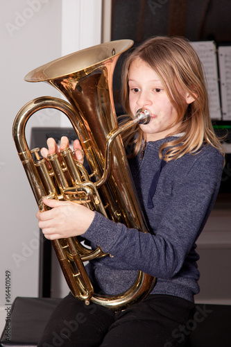 Photo Young girl blowing on a baritone horn.