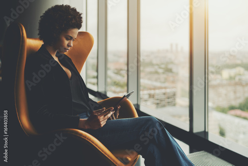 Obraz Cute pensive afro american student is sitting on armchair in front of window of skyscraper and having online conversation with her curator during probation period in office via digital tablet - fototapety do salonu
