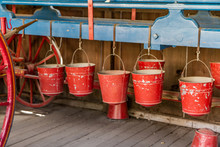 Old-Fashioned Red Fire Buckets Hanging On A Blue Rail