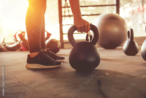 Photo Stands Fitness Fitness training with kettlebell in sport gym with sunlight effect.