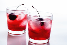 Red Drink With A Cherry In A Glass With Ice On A White Background.