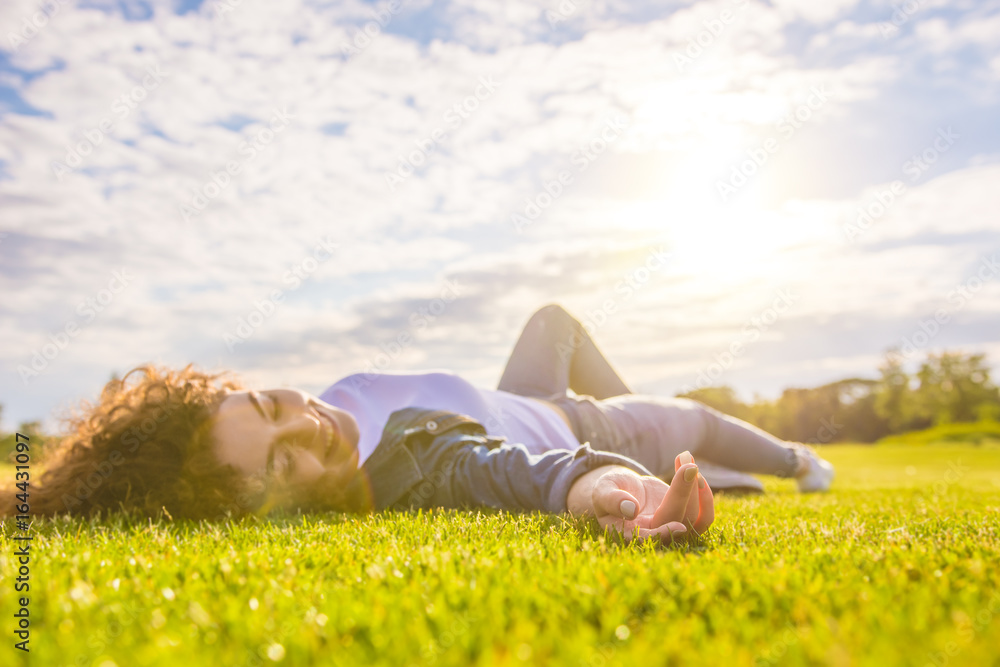 Fototapeta The happy woman lay on the grass against the background of the sunshine