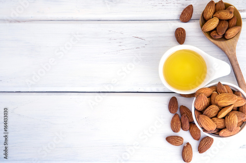 Fototapeta Close up almond oil in the bottle and almond seed in white cup for oil massage and spa treatment ingredient on the white wooden table background , top view or over head shot with copy space obraz