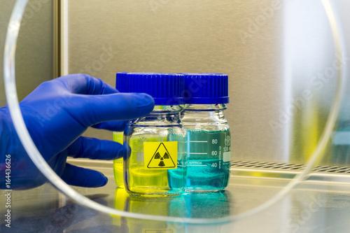 Fotografia hand grasps a radioactive sample in a laboratory environment