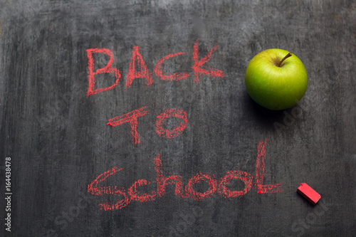"Valokuva  ""back to school"" inscription in red chalk on a black chalk Board and a green app"