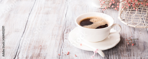 Fototapeta White cup of coffee with pink flowers on old white wooden background with copy space. obraz