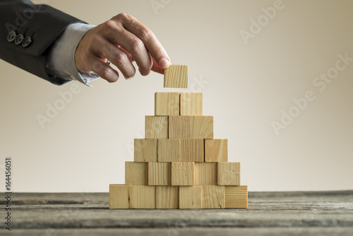 Businessman making a pyramid with empty wooden cubes Fototapeta
